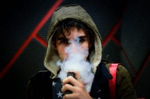 Young man in hoodie vaping; image by Nery Zarate, via Unsplash.com.