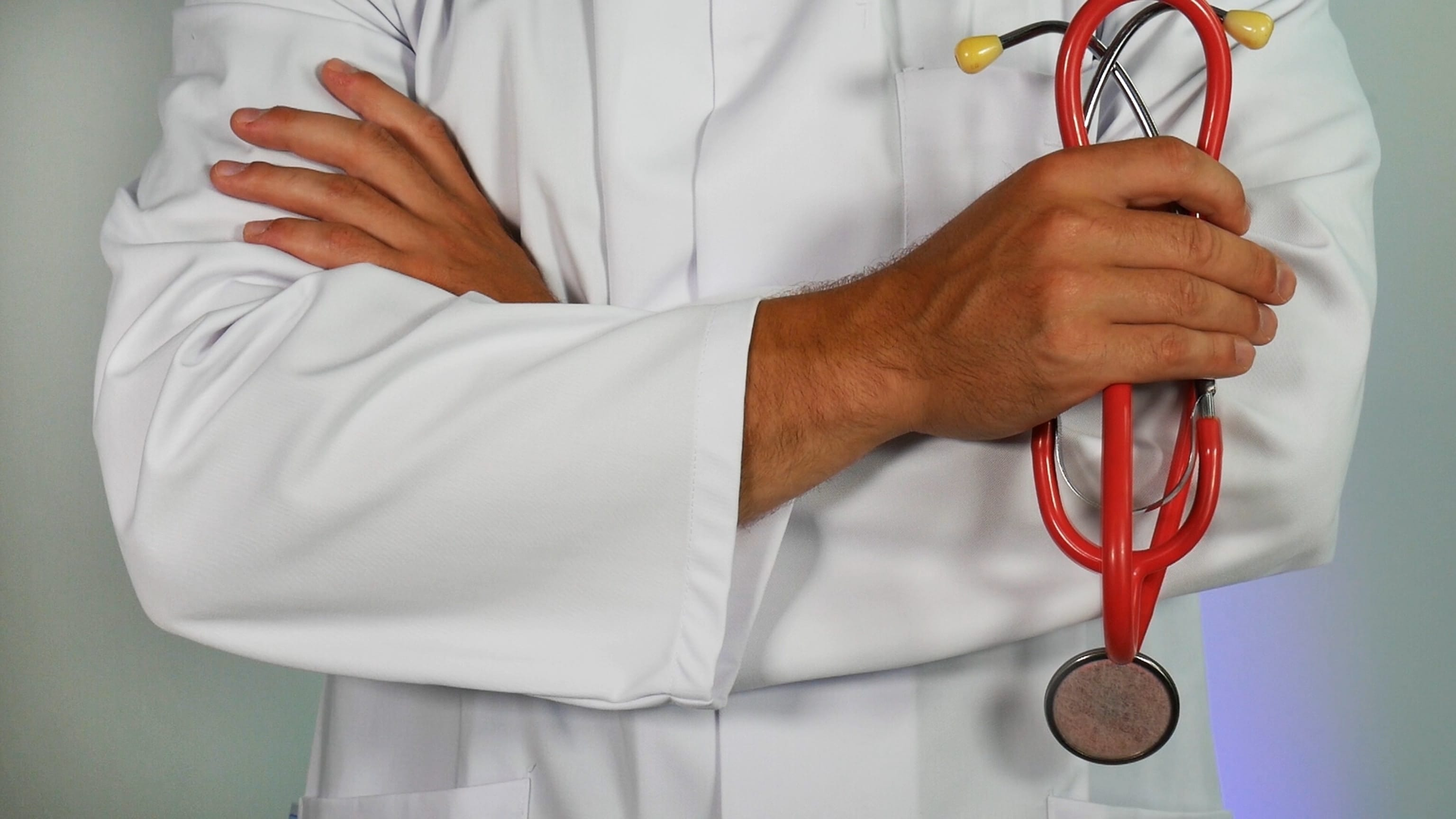 Doctor holding red stethoscope; image by Online Marketing, via Unsplash.com.
