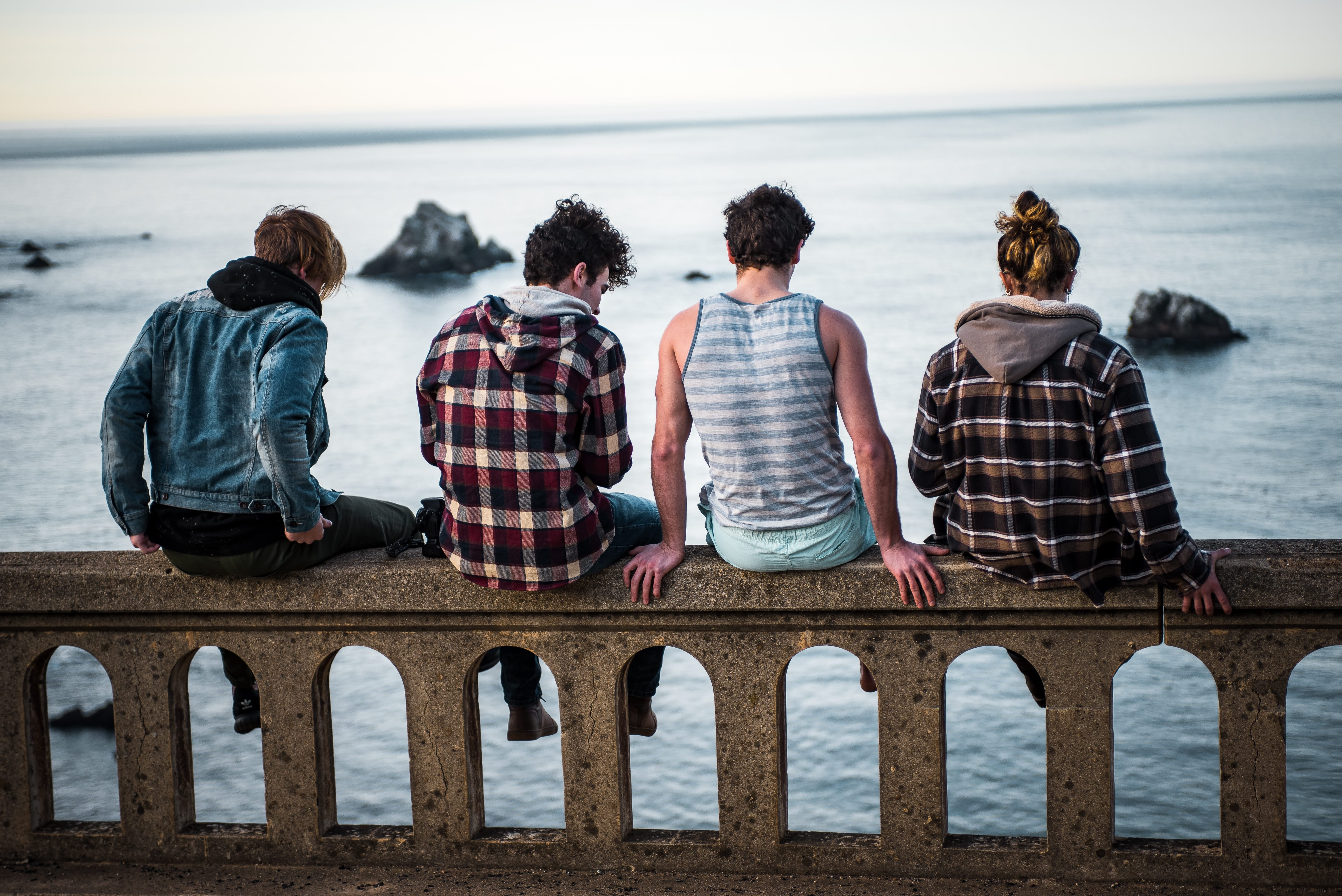 Four teens sitting on bench in front of body of water; image by Sammie Vasquez, via Unsplash.com.