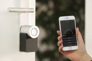 Nuki smart lock with iPhone; image by Sebastian Scholz (Nuki), via Unsplash.com.