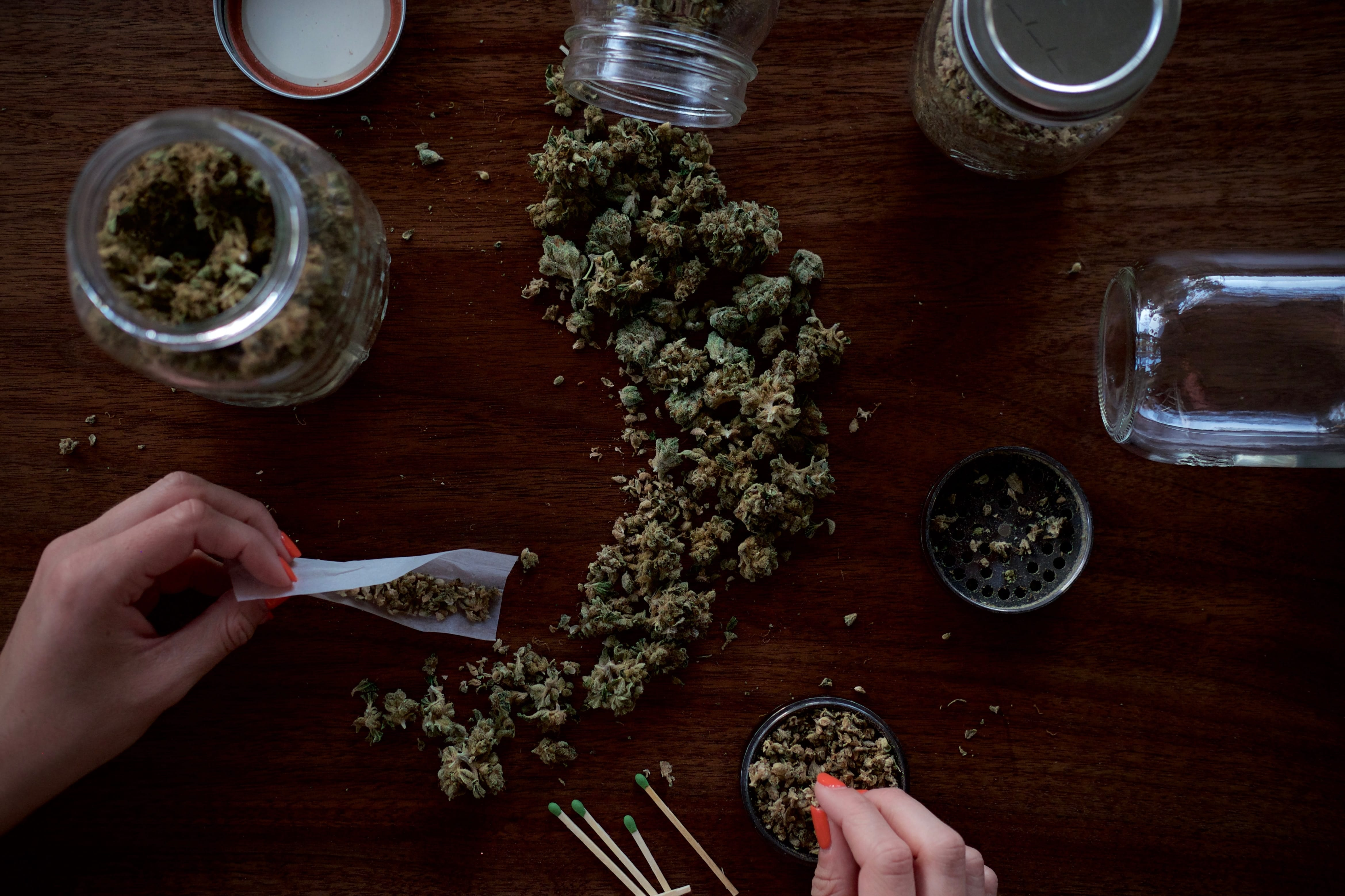 Woman with rolling paper and marijuana on brown table; image by Wesley Gibbs, via Unsplash.com.