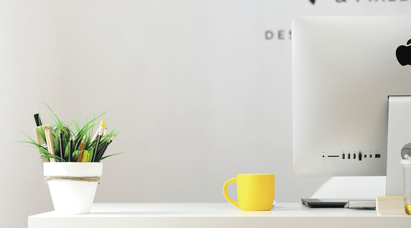 Yellow ceramic mug on white desk next to computer and plant; image by Georgie Cobbs, via Unsplash.com.