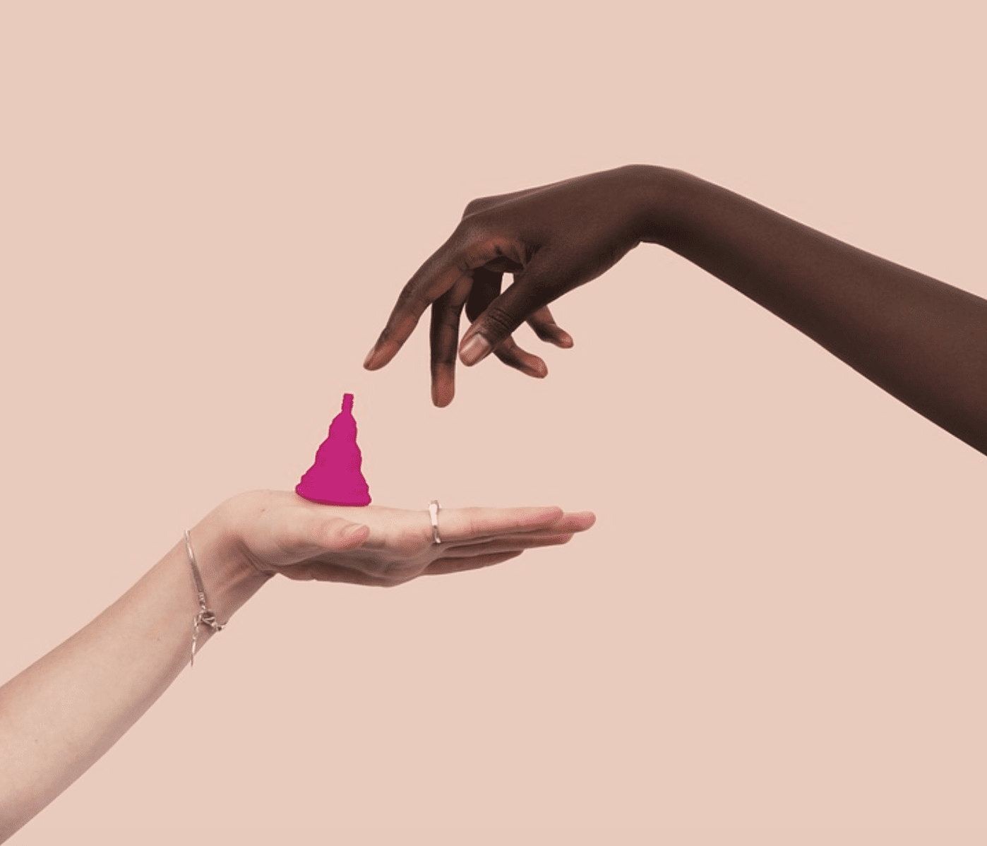 Two women's hands, one balancing a menstrual cup; image by PatriciaMoraleda, via Pixabay.com.