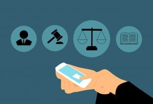 Graphic of person using smartphone to access the scales of justice; image via piqsels.com CCO.