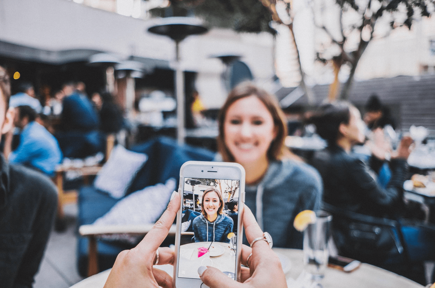 Person taking smartphone picture of young woman seated across the table from them; image via Unsplash.com.