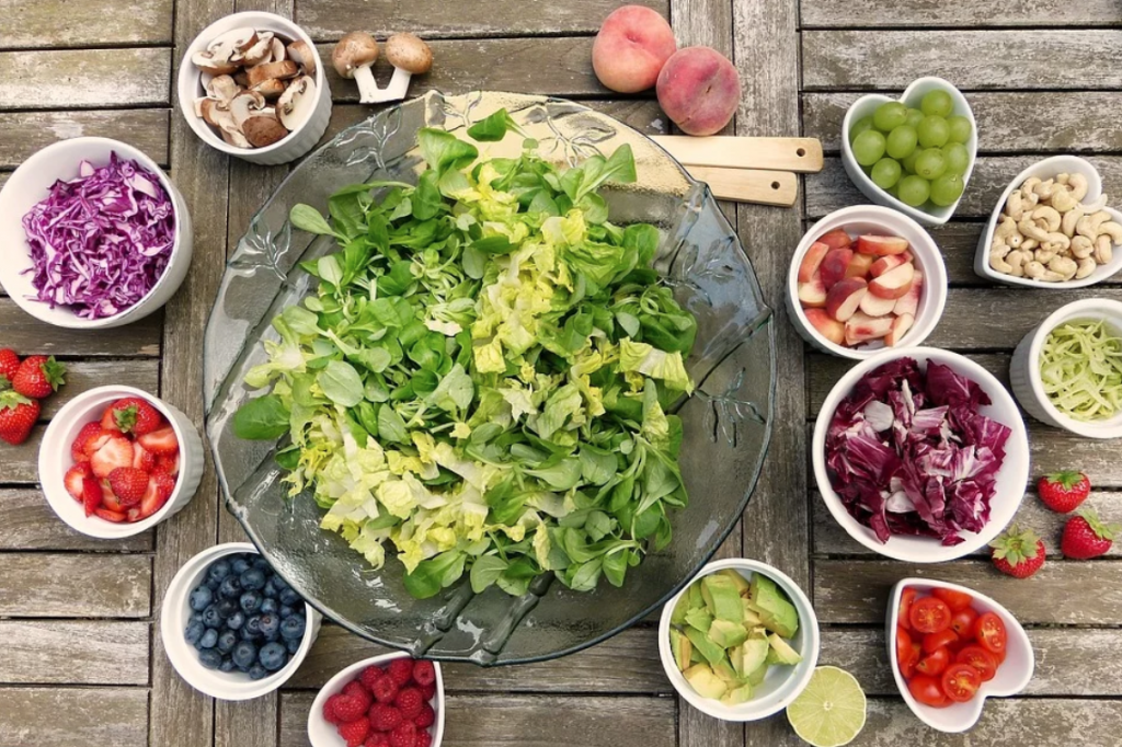 Big bowl of shredded lettuce surrounded by smaller bowls of salad items; image by Silviarita, via Pixabay.com.
