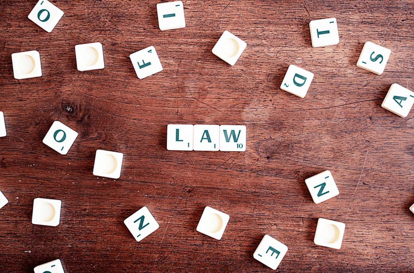 "Scrabble tiles, some of which spell ""Law."" Image by CQF-Avocat, via Pexels.com."