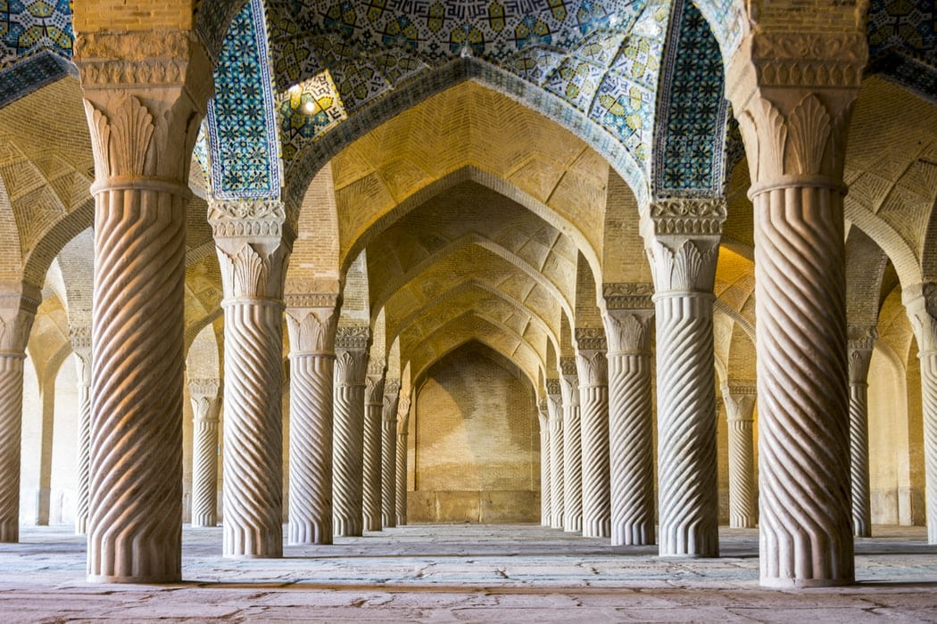 Aesthetically pleasing view of columns and pointed arches in a well-lit, delicately decorated mosque.