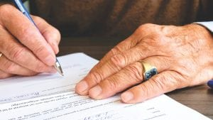 Man signing paperwork; image via Pexels.com.