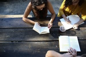 Three people studying at an outdoor table; image by Alexis Brown, via Unsplash.com.