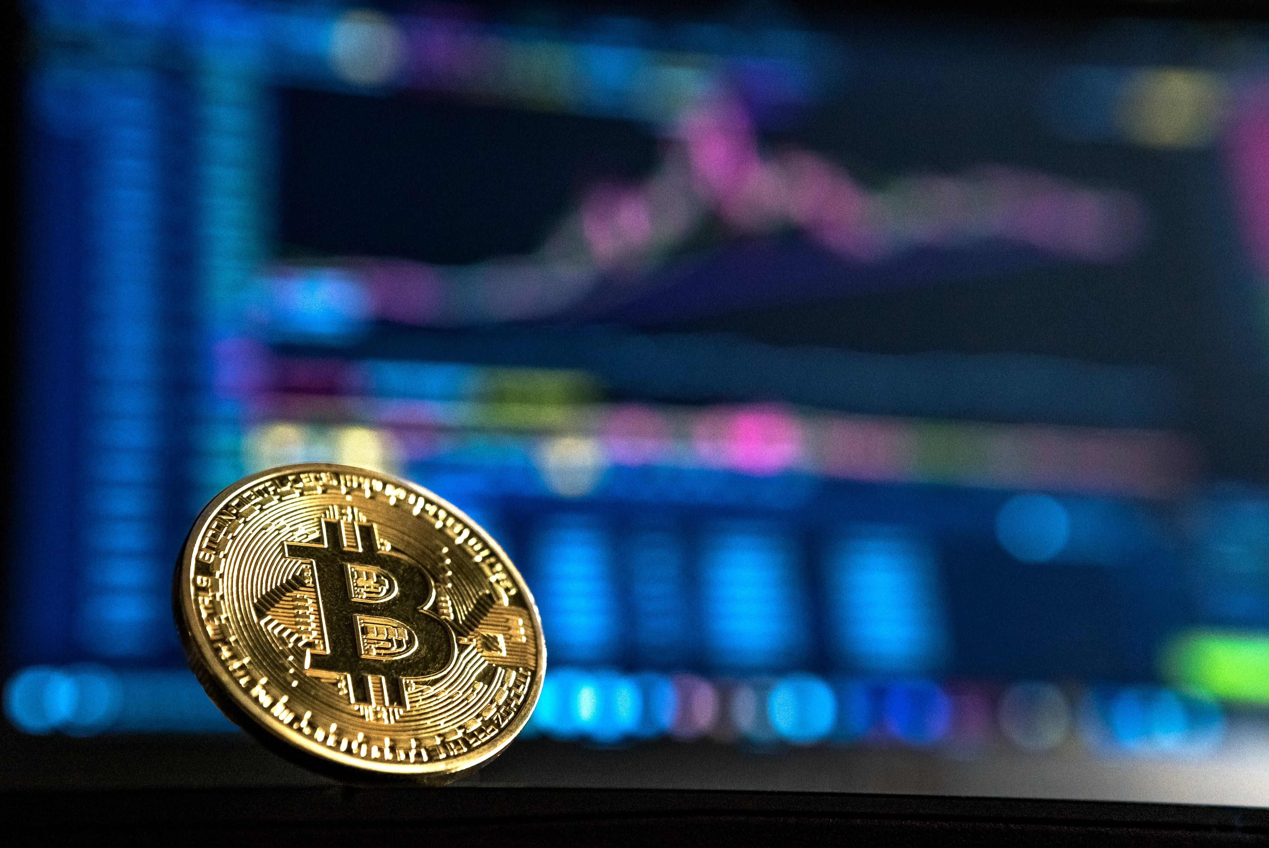 A gold bitcoin on a soft focus multi-colored background; image by André François McKenzie, via Unsplash.com.