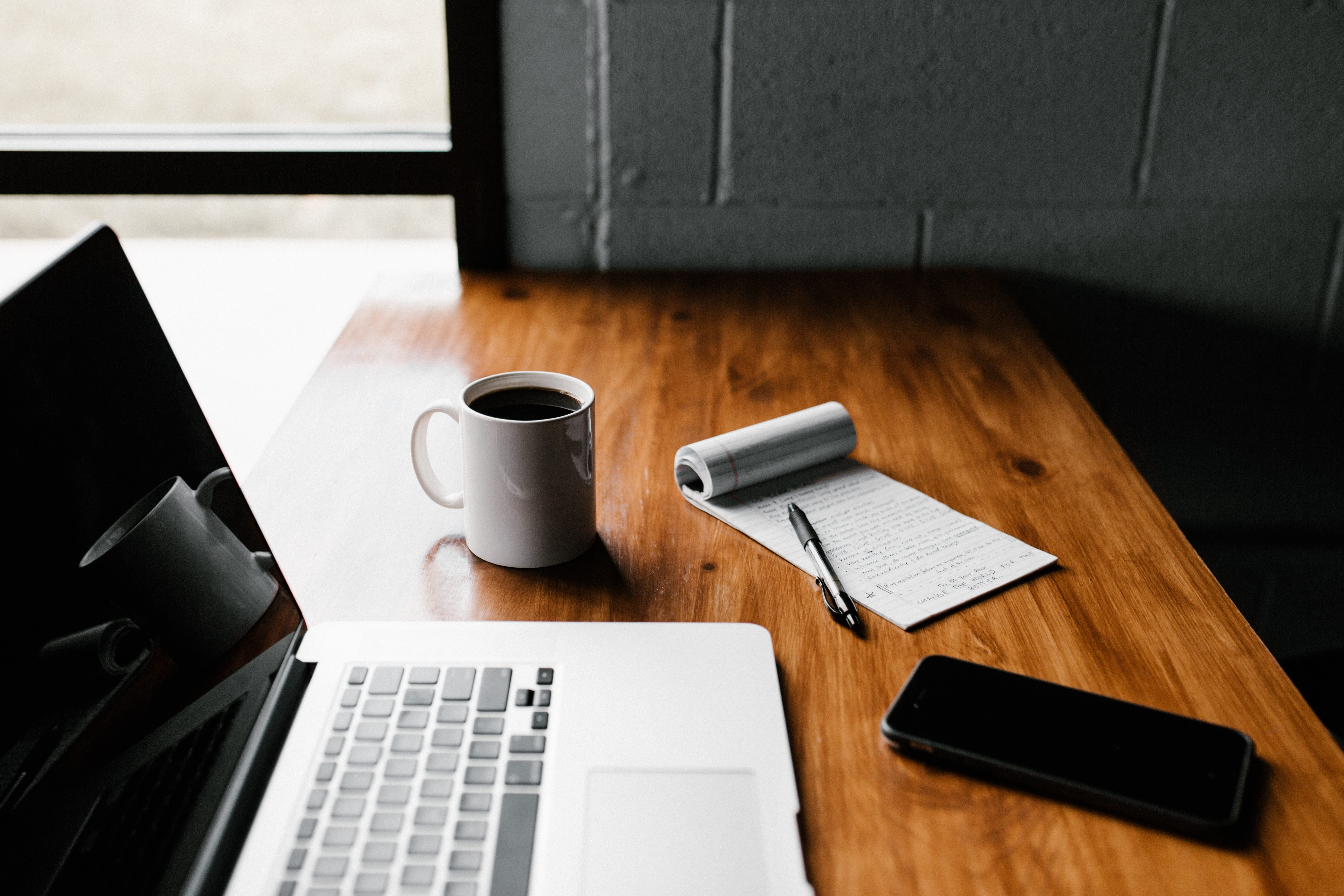 MacBook Pro, white ceramic mug,and black smartphone on table; image by Andrew Neel, via Unsplash.com.