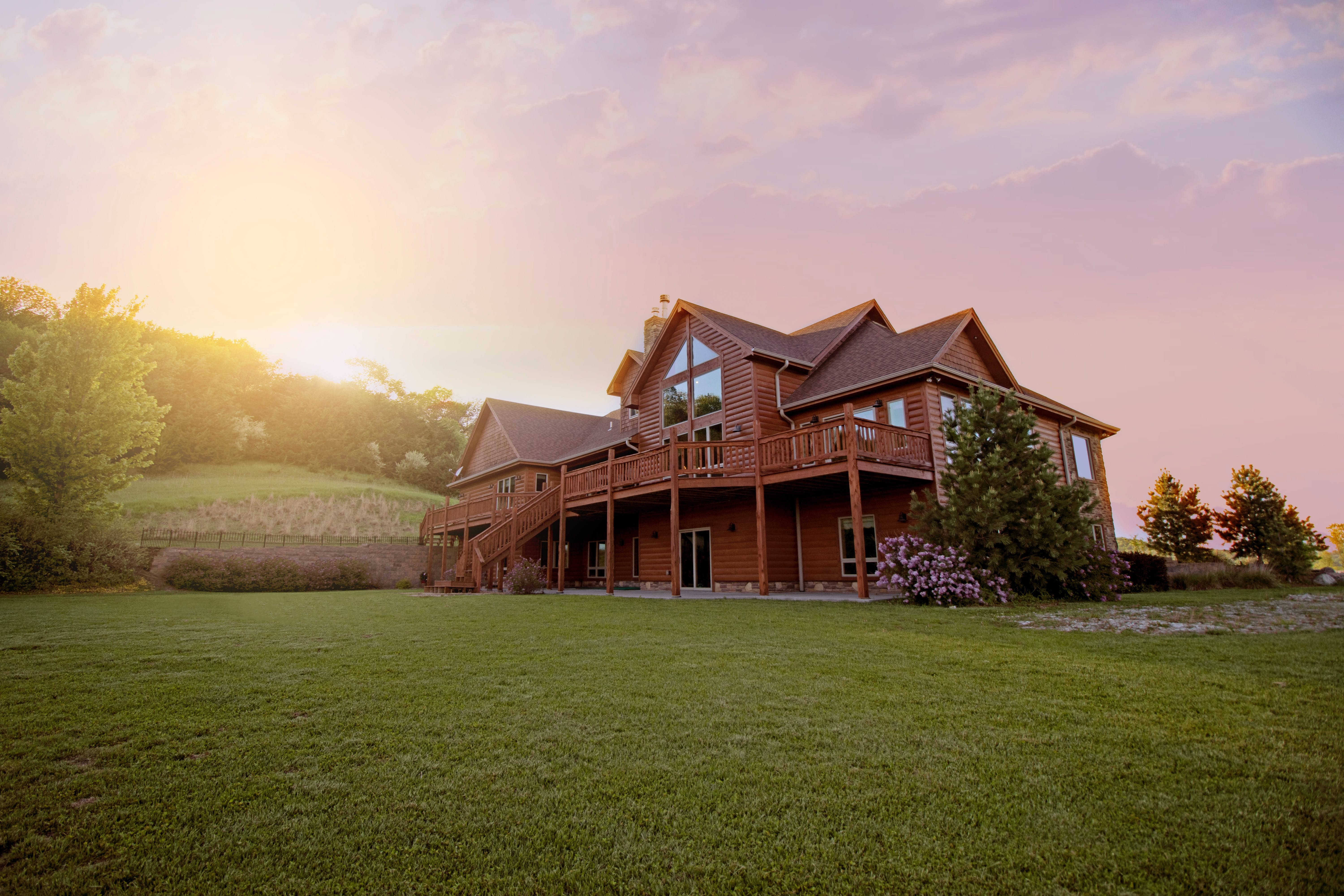 Brown wooden house with green grass field; image by Bailey Anselme, via Unsplash.com.