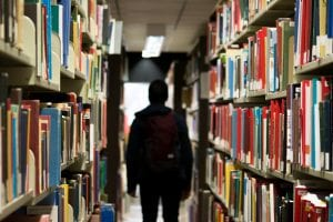 Male student with backpack walking between library shelves; image by Bantersnaps, via Unsplash.com.
