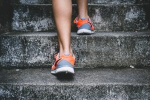 Person wearing orange and gray Nike shoes walking on gray concrete stairs; image by Bruno Nascimento, via Unsplash.com.