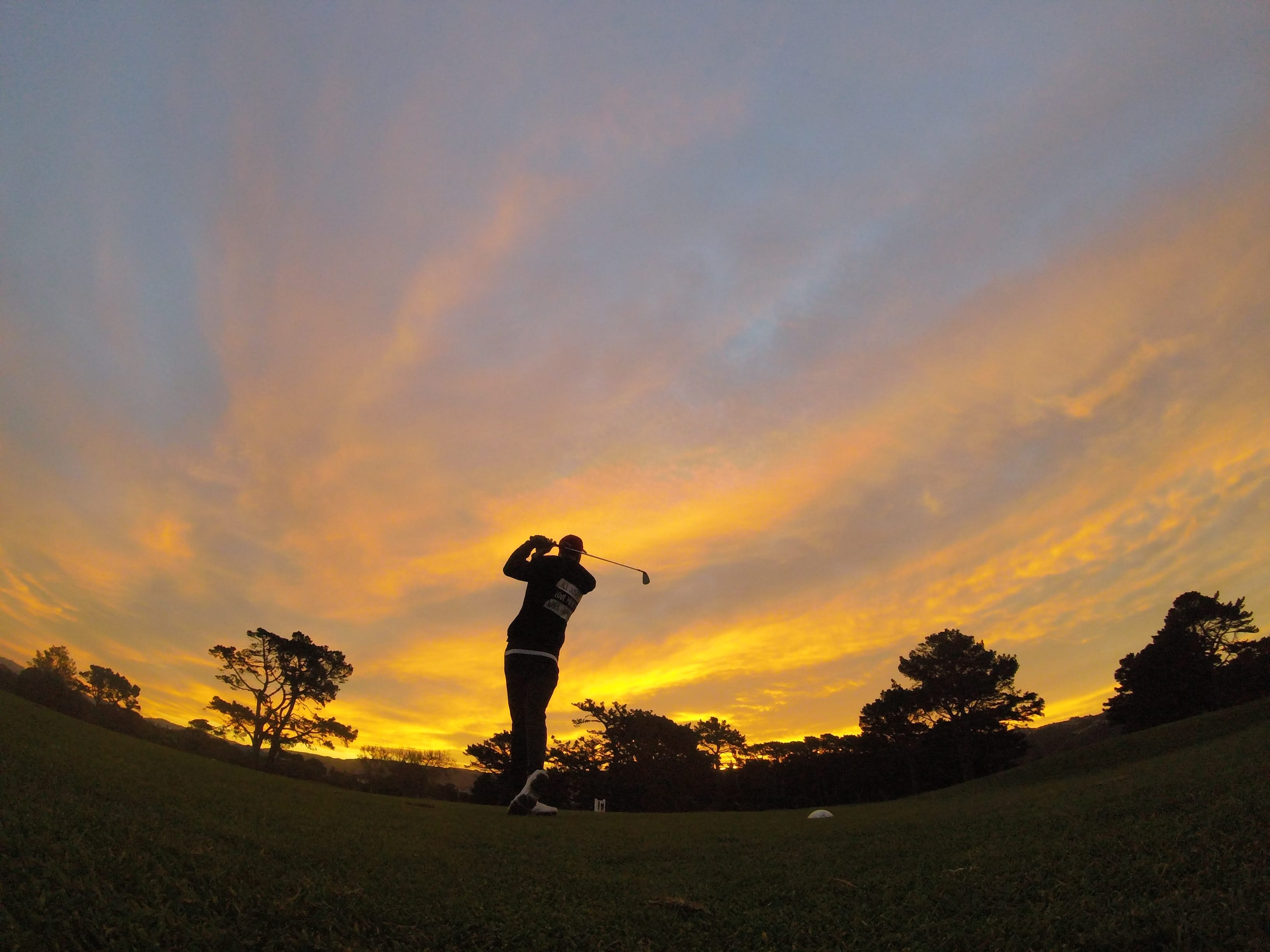 Silhouette of man swinging golf club at sunset; image by David Goldsbury, via Unsplash.com.