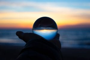 Person holding clear glass ball at sunrise; image by Drew Beamer, via Unsplash.com.