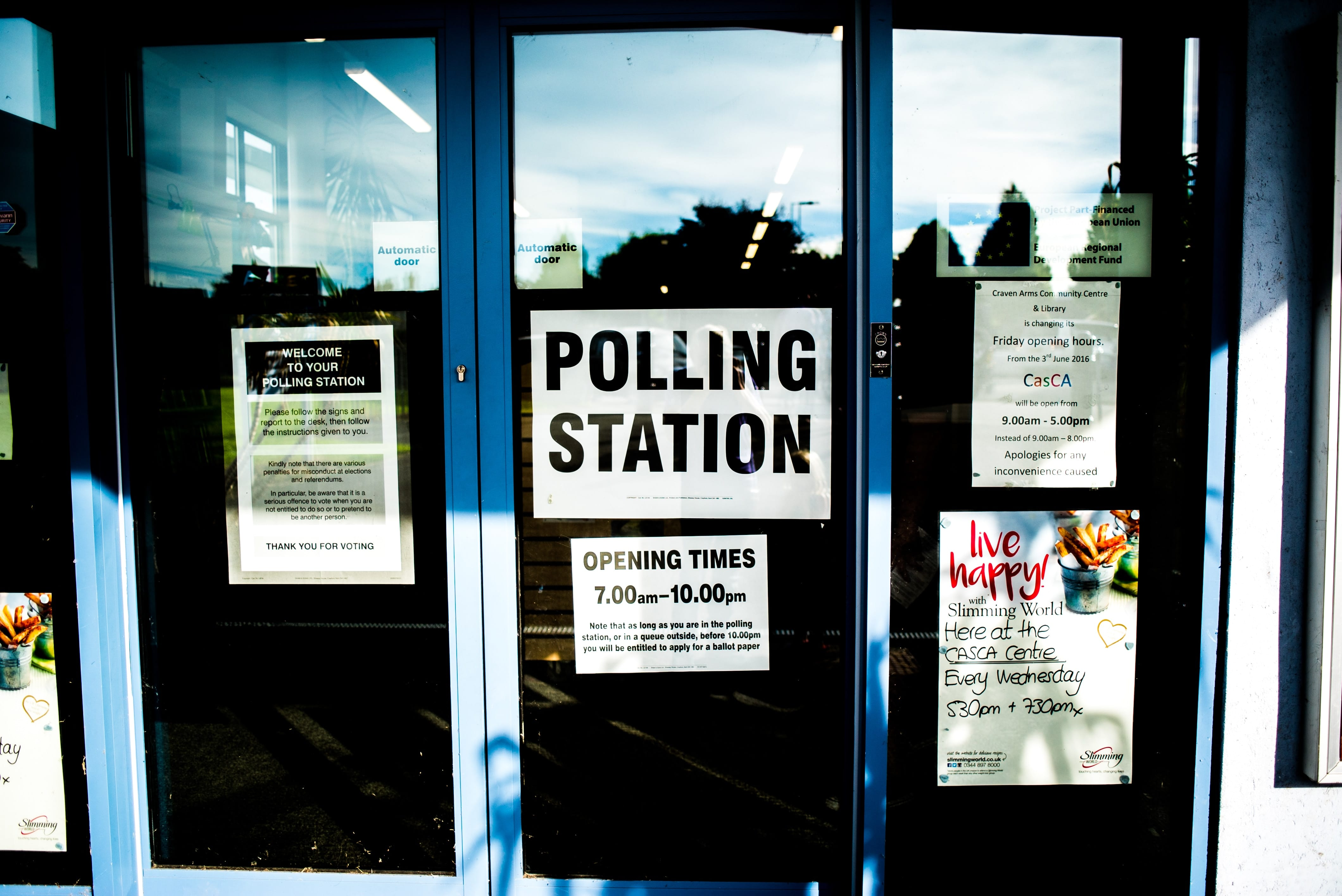 Polling station sign on glass door; image by Elliot Stallion, via Unsplash.com.