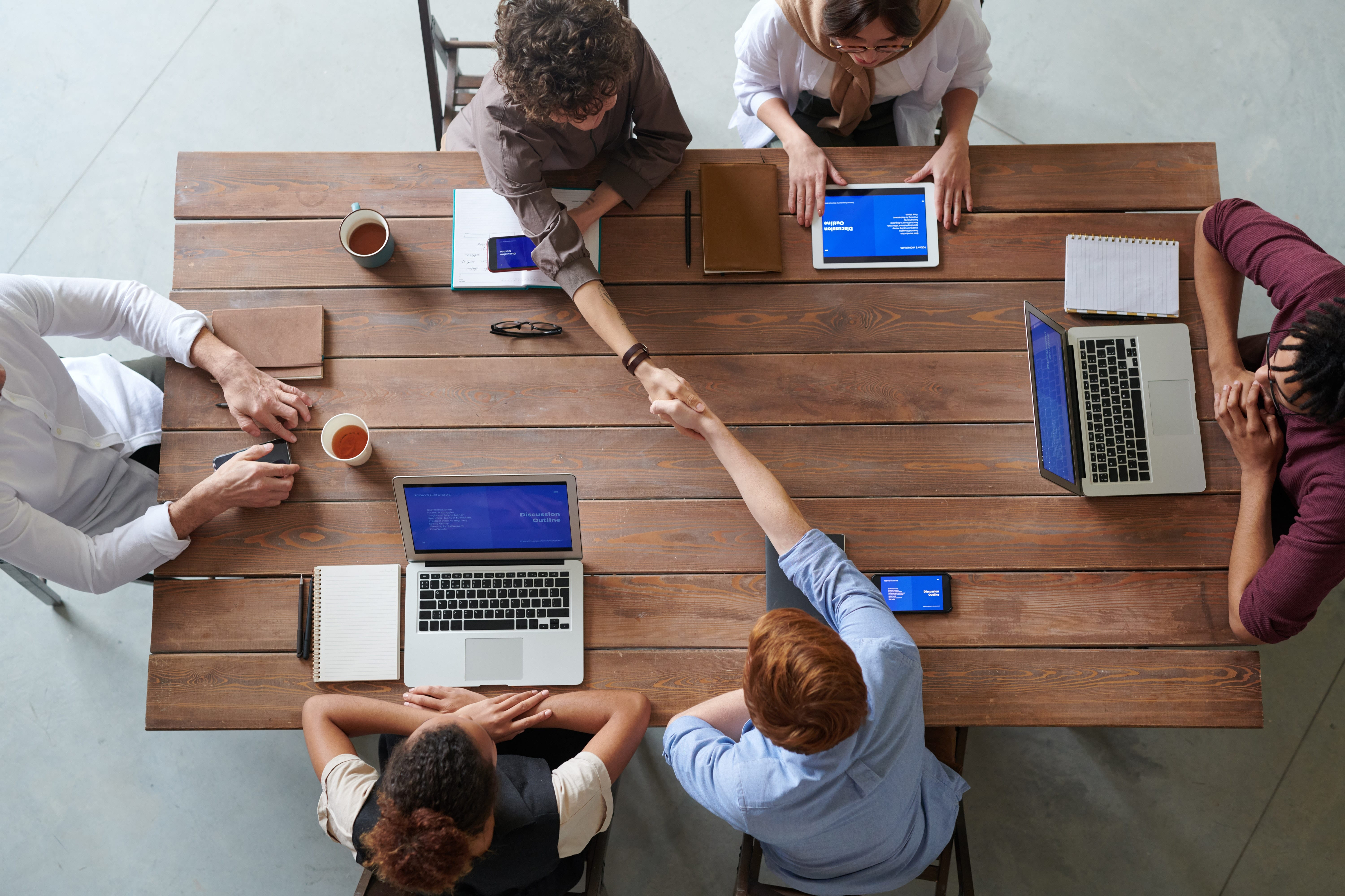 Group of people with laptops having meeting at brown wooden table; image by Fauxels, via Pexels.com.