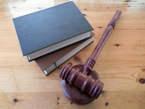 Gavel and two hardbound books on wooden table; image by Succo, via Pixabay.com.