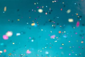 Colorful confetti falling down with a teal background; image by Jason Leung, via Unsplash.com.