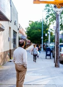 Man on sidewalk watching woman walk away with her bags; image by Jurien Huggins, via Unsplash.com.