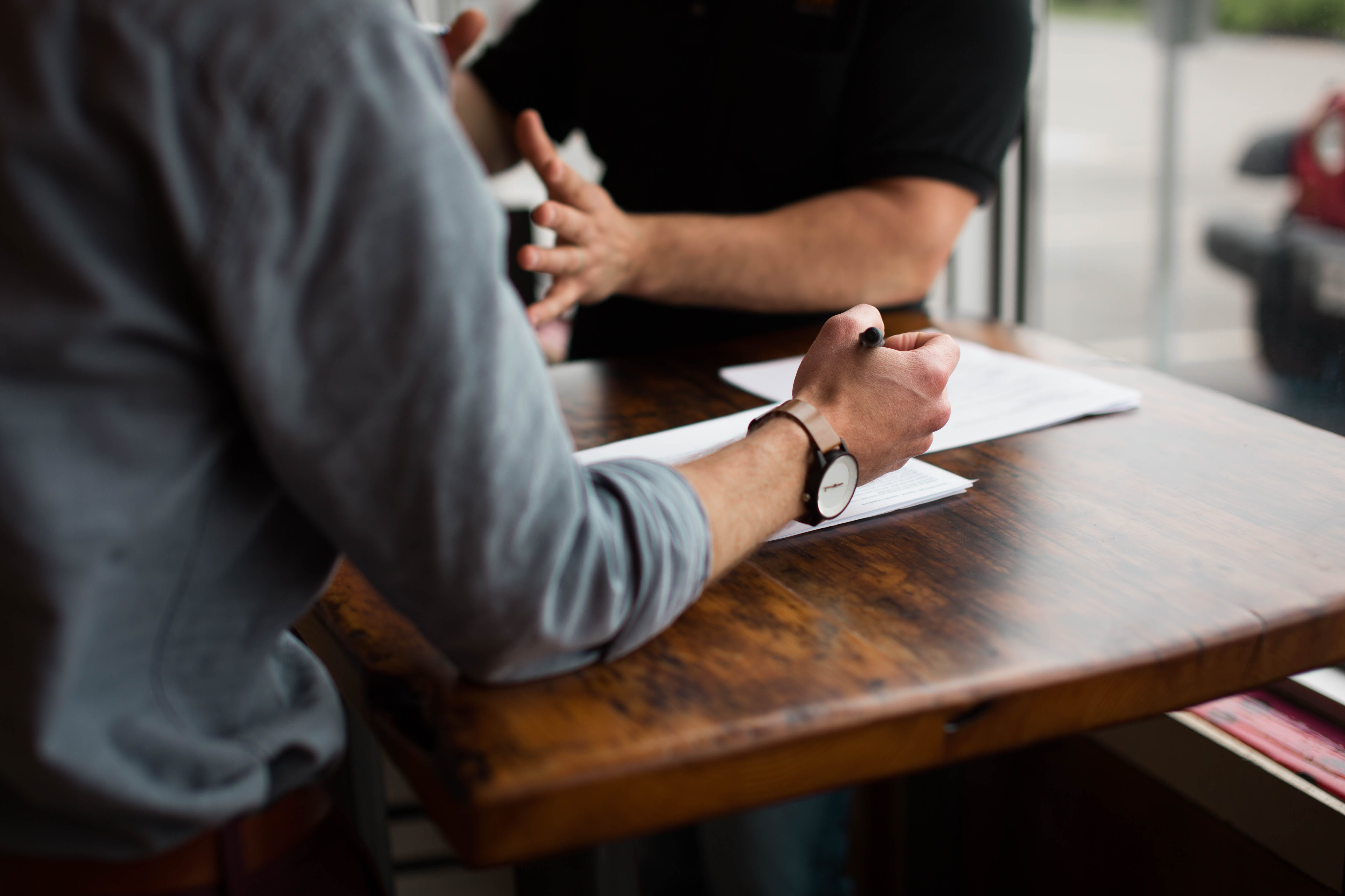 Two men reviewing documents at brown wooden table; image by Nik MacMillan, via Unsplash.com.