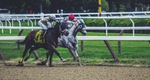 Two jockeys & horses in a close race; image by Noah Silliman, via Unsplash.com.