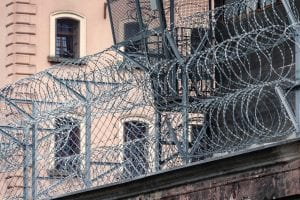 Gray barbwire on fence near building; image by Paweł Czerwiński, via Unsplash.com.