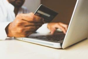 Man holding credit card shopping via laptop; image by rupixen.com, via Unsplash.com.