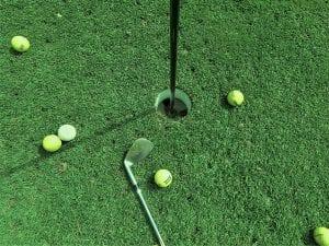 Six golf balls near hole and one golf club; image by TSG Pixels, via Unsplash.com.