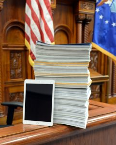 A tablet leans on a stack of legal documents.