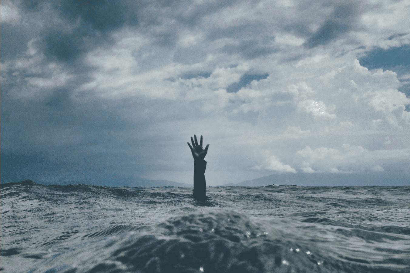 Person's arm and hand reaching up from under water; image by Nikko Macaspac, via Unsplash.com.
