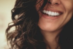 Woman smiling close-up photography; image by Lesly Juarez, via Unsplash.com.