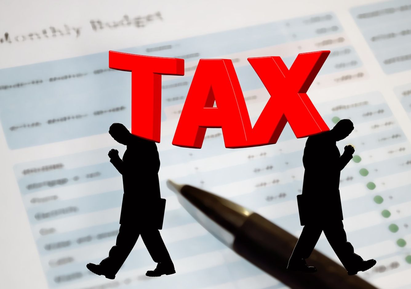 "Budget paper and pen with silhouettes of two men walking away from each other and the word ""Tax"" in bold red letters; image by Geralt, via Pixabay.com."