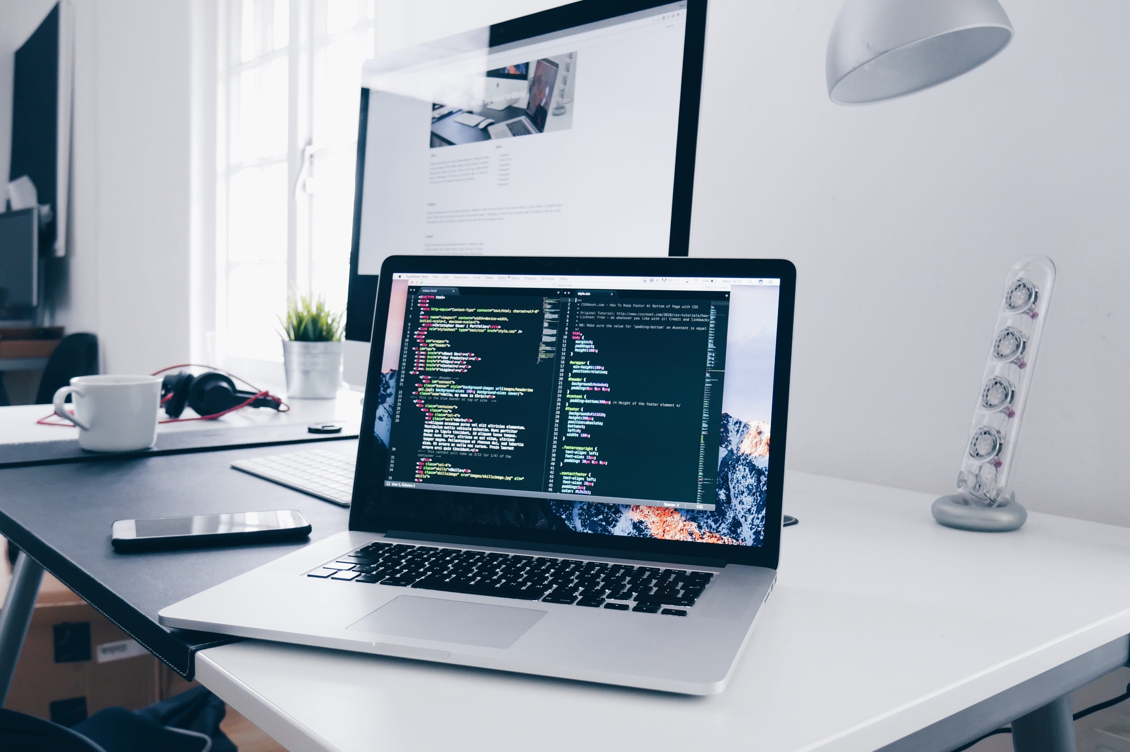 MacBook with lines of code on its screen on a desk; image by Christopher Gower, via Unsplash.com.