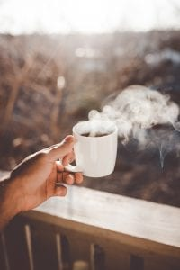 Man holding white ceramic cup with steaming hot coffee; image by Clay Banks, via Unsplash.com.