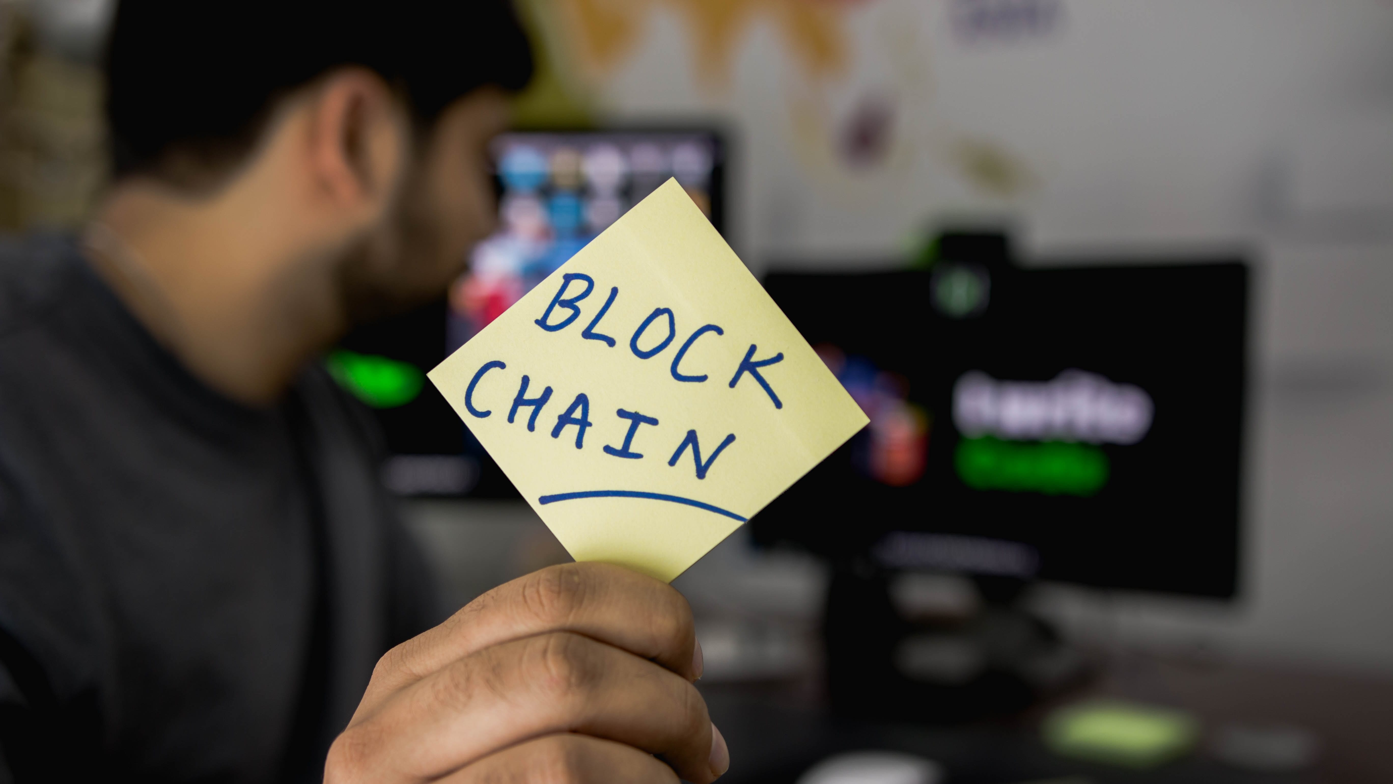 "Man holding sticky note with ""Blockchain"" written on it; image by Hitesh Choudhary, via Unsplash.com."