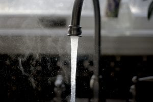 Greyscale photo of running faucet; image by Imani, via Unsplash.com.