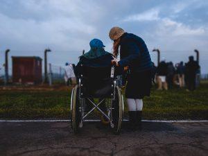 Woman standing near person in wheelchair near green grass field; image by Josh Appel, via Unsplash.com.