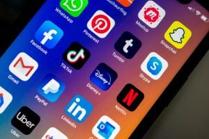 iPhone displaying social media apps; image by Kon Karampelas, via Unsplash.com.