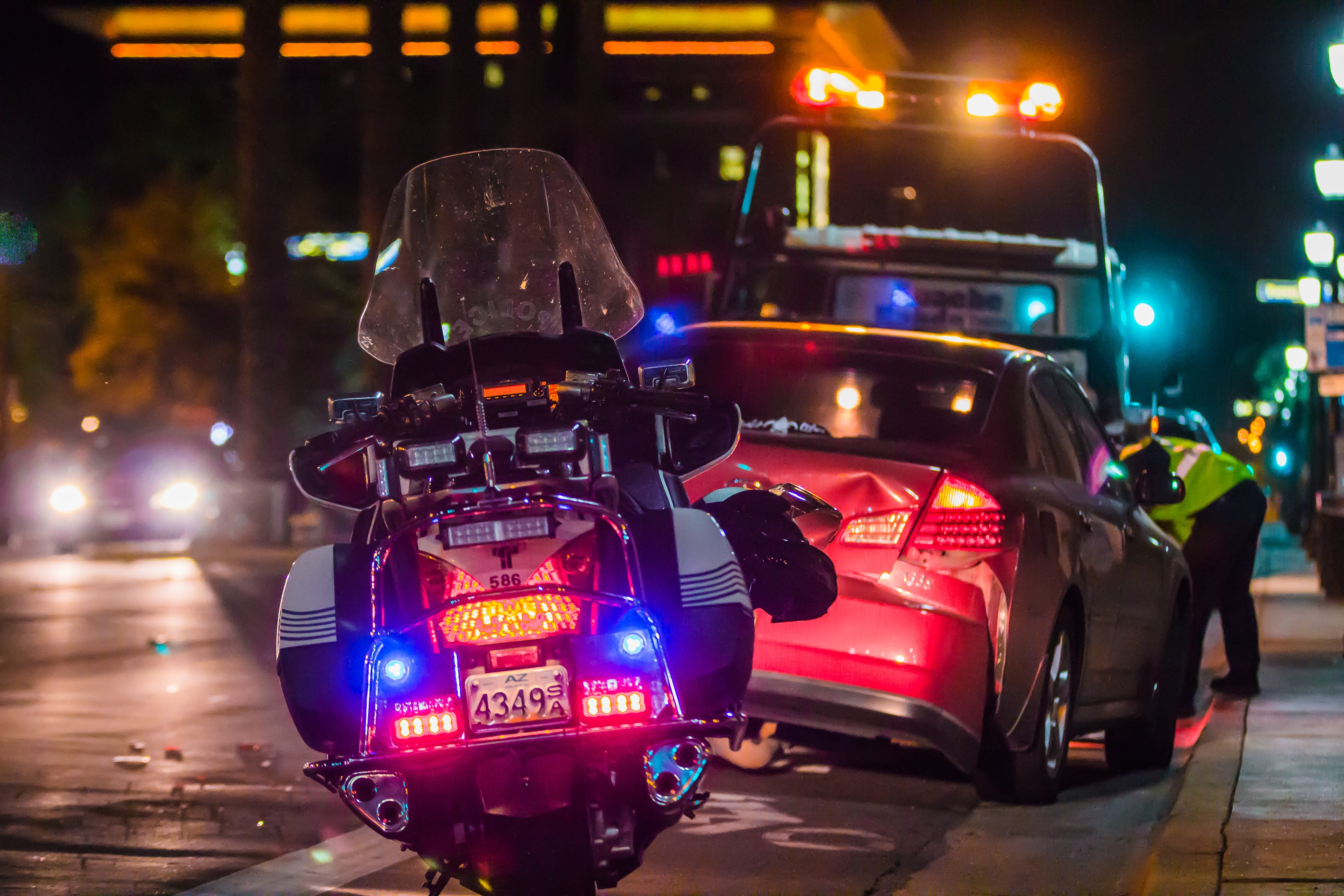 Police officer leaning in window of car after accident; image by Matt Chesin, via Unsplash.com.
