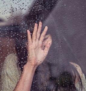 Woman touching raindrop covered window pane; image by Milada Vigerova, via Unsplash.com.
