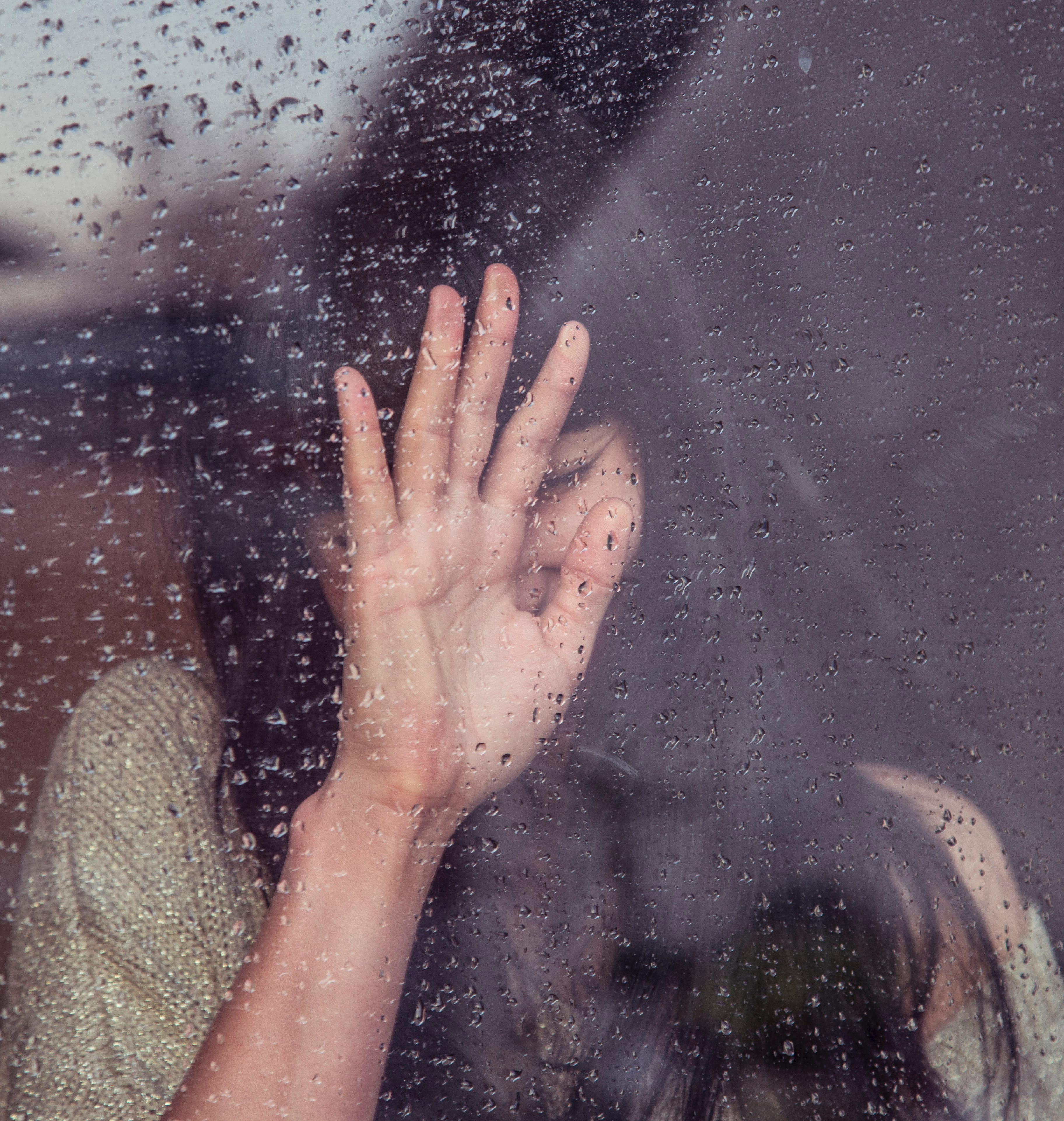 Woman touching raindrop covered window pane; image by Milada Vigerova, via Unsplash.com.