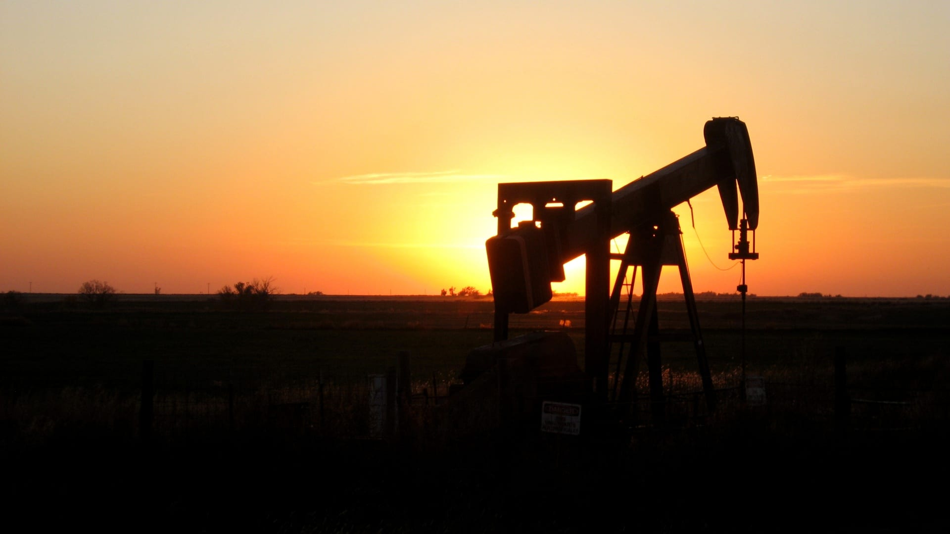 Orange sky and the sun near the horizon, silhouetting an oil pump in the foreground.