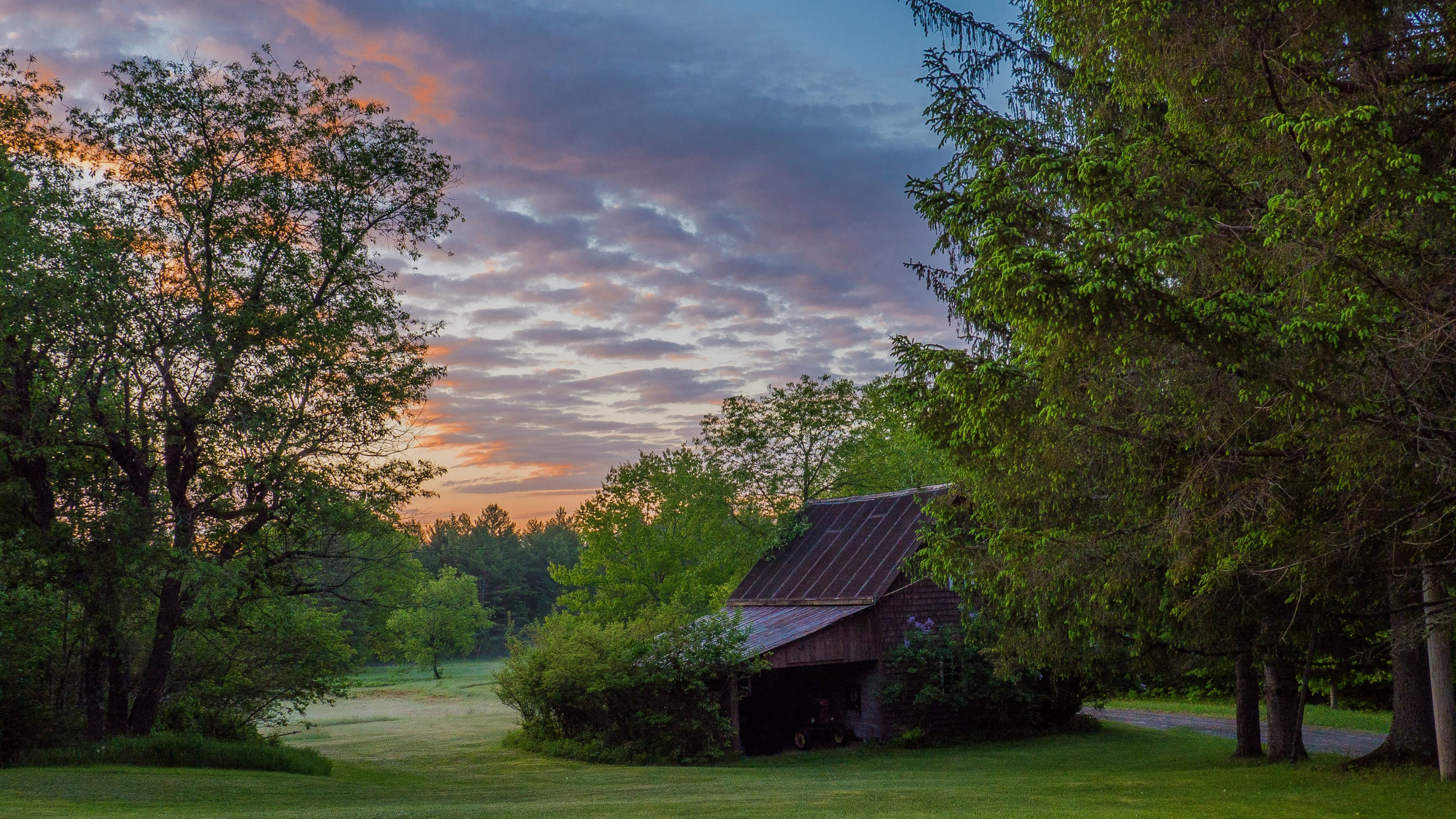 Red house surrounded by trees at dawn; image by Paul Varnum, via Unsplash.com.