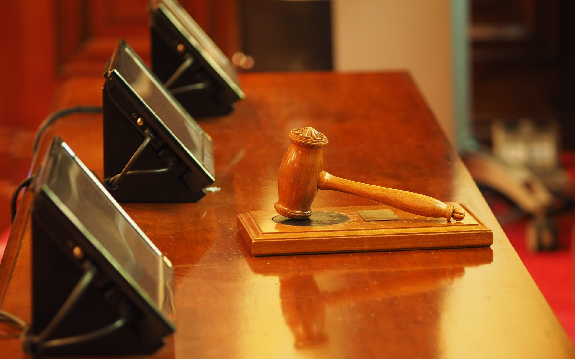 A gavel lays on a wooden table with monitor screens nearby.