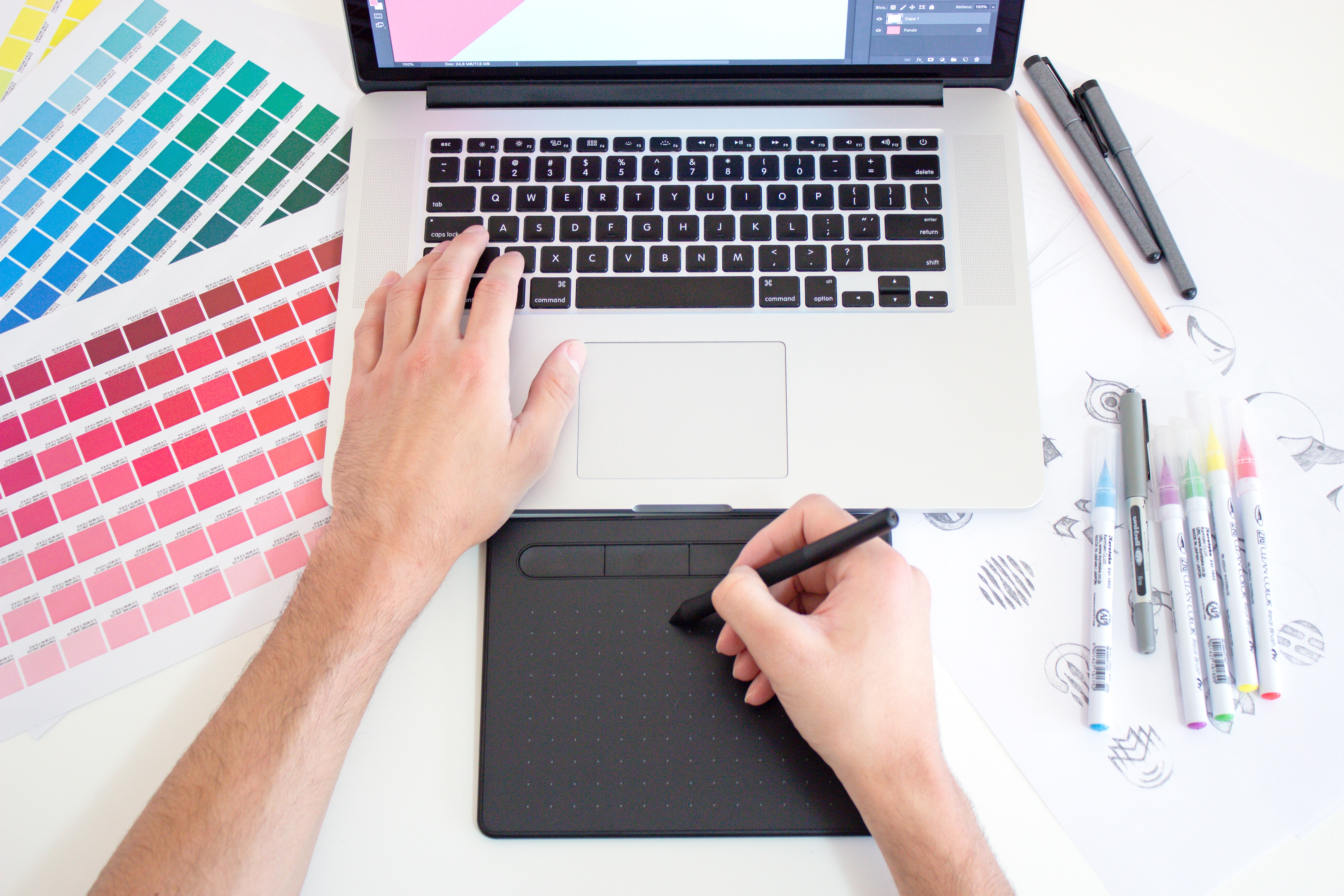Graphic designer working on a Macbook laptop using a trackpad, color charts and markers; image by Theme Photos, via Unsplash.com.