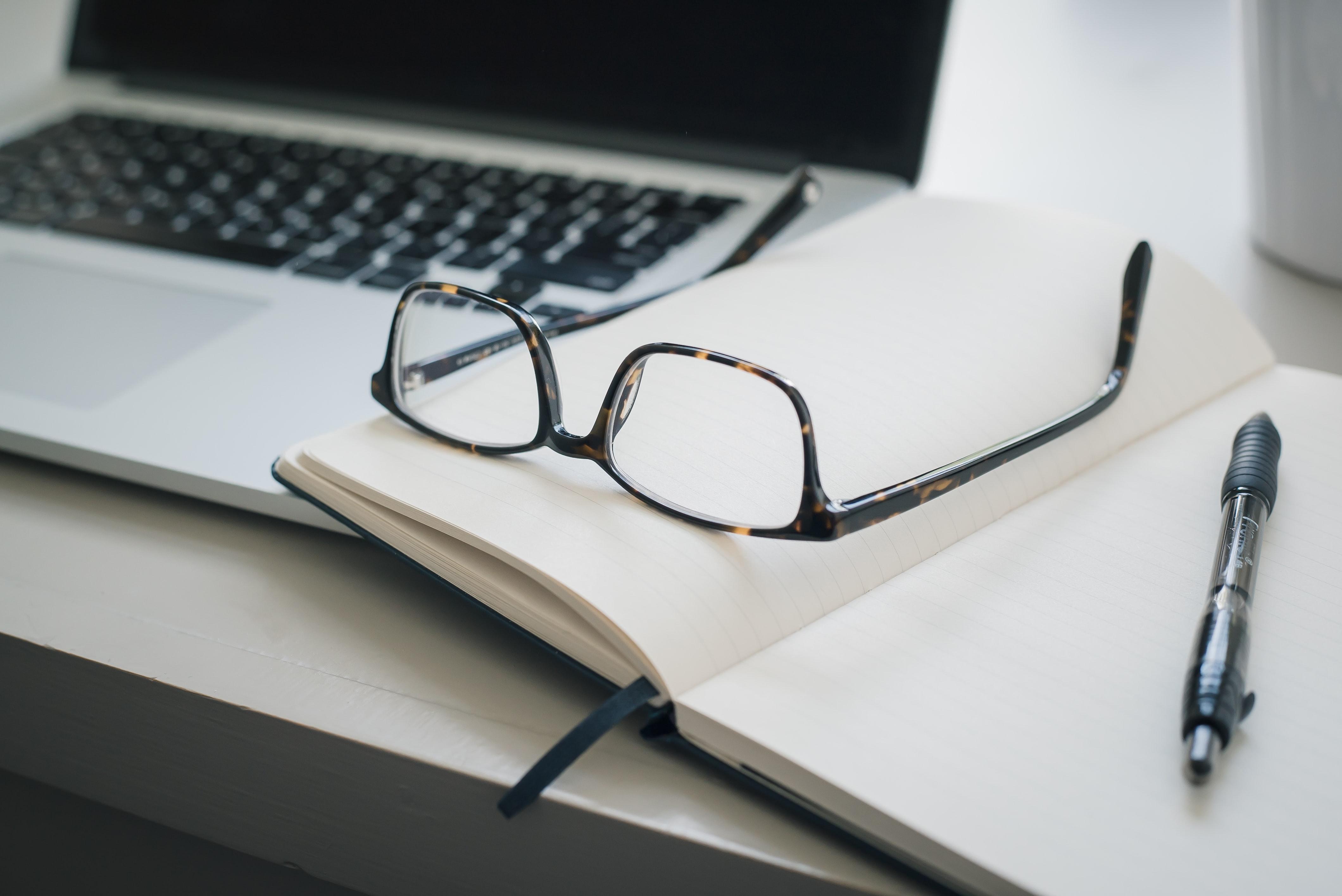 Black framed eyeglasses and black pen next to laptop; image by Trent Erwin, via Unsplash.com.