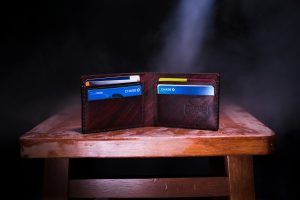 Handmade brown leather wallet with credit cards sitting on brown wooden stool; image by Two Paddles Axe and Leatherwork, via Unsplash.com.